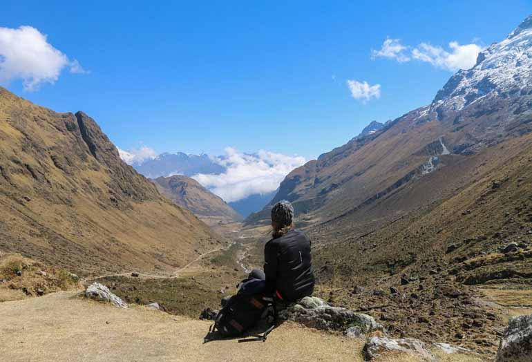Sitzender Oberkörper von hinten mit Bergen im Hintergrund.