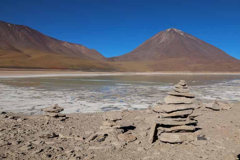 Steinplattenturm mit Lagune und Berg im Hintergrund.