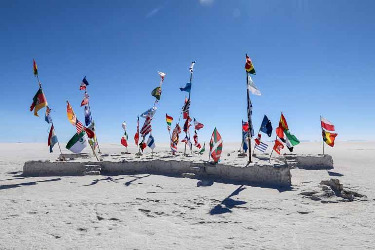 In der Salar de Uyuni: Viele verschiedene Flaggen auf einem Stein.