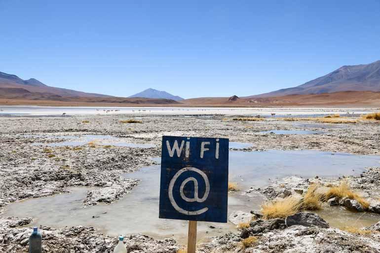 Schild mit der Beschriftung WiFi steht von einer Lagune mit Flamingos.