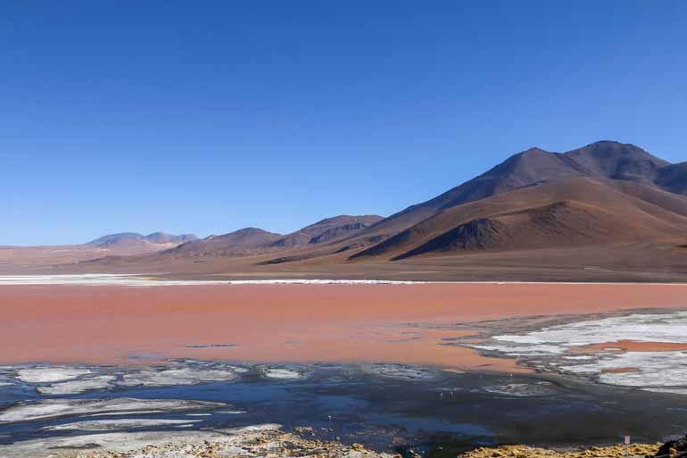 Eine Lagune mit rotem Wasser und Bergen im Hintergrund.