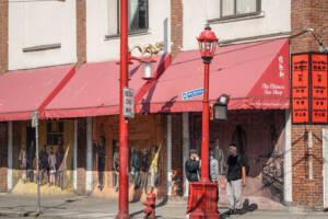Vancouver: Rote Markisen zieren die Hausmauern mit Graffiti in Chinatown, davor stehen Menschen
