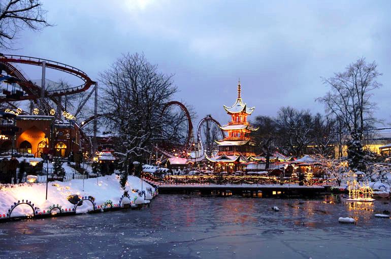 Weihnachtsmarkt hinter einem See, dahinter eine Achterbahn