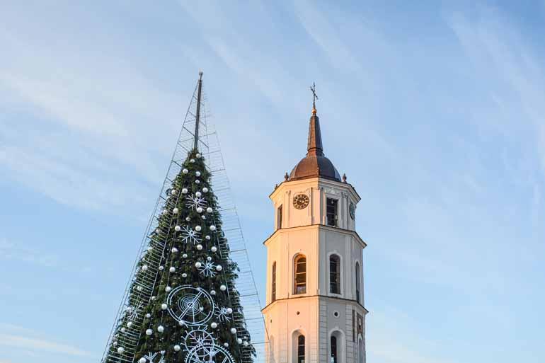 Oberer Teil vom Glockenturm, daneben die Spitze eines Weihnachtsbaums.