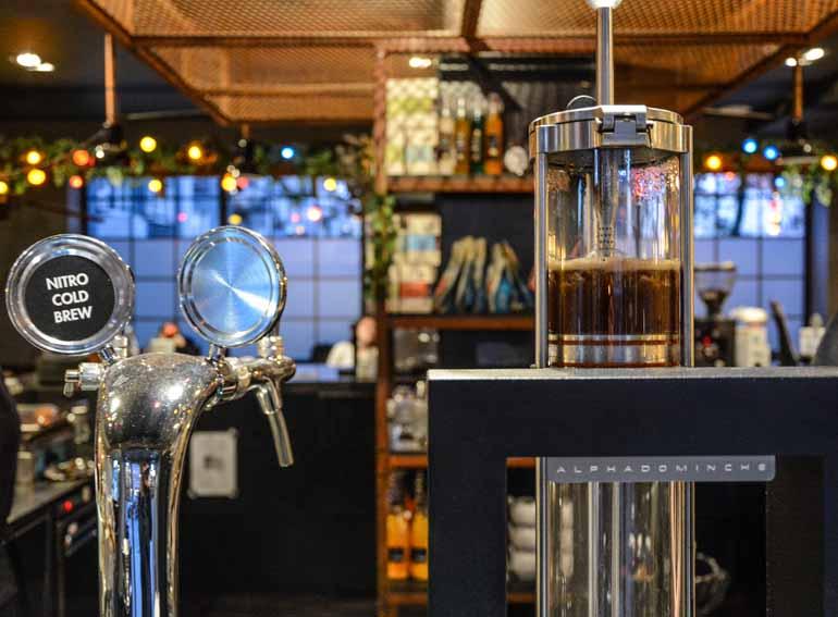 Eine Kaffeemaschine neben einem Zapfhahn.