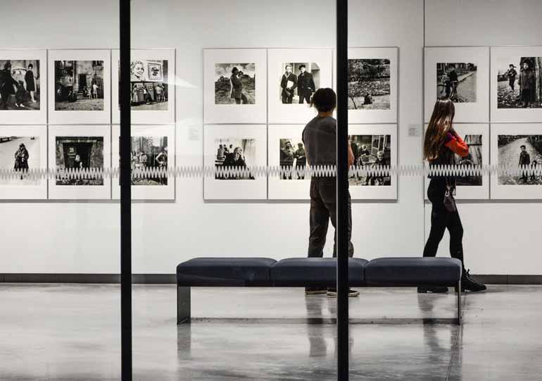 Eine Fotoausstellung mit zwei Menschen im Hintergrund.
