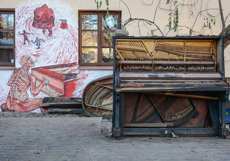 Klavier vor einer Hausmauer.