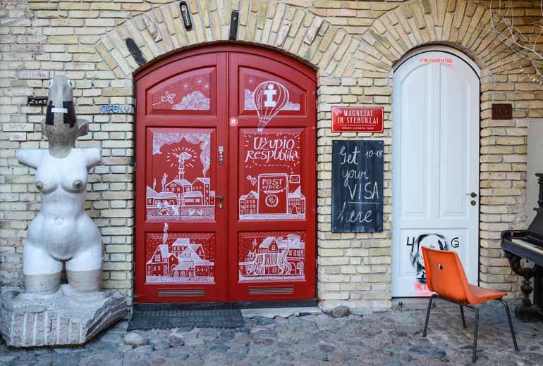 Einer Rote Tür mit einer Skulptur neben dran.
