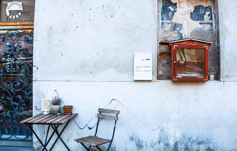 Ein Tisch und ein Stuhl stehen vor einer Hausmauer.