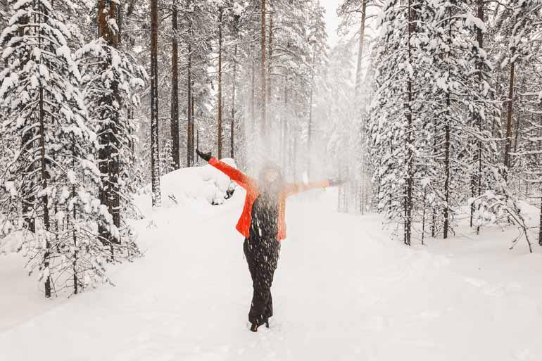 Eine Frau steht in einer Schneelandschaft in Finnisch Lappland.