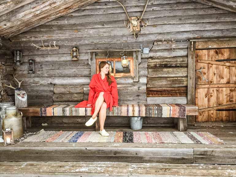 Frau sitzt vor einer Sauna Hütte in Finnisch Lappland.