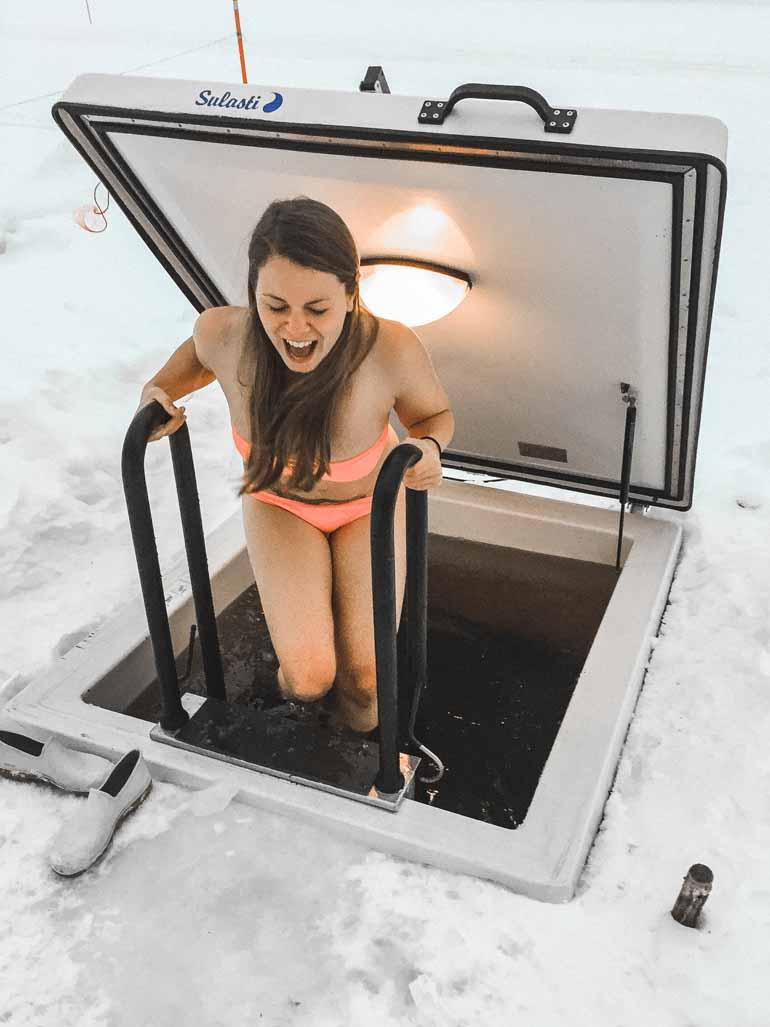 Eine Frau beim Eisbaden in Finnisch Lappland