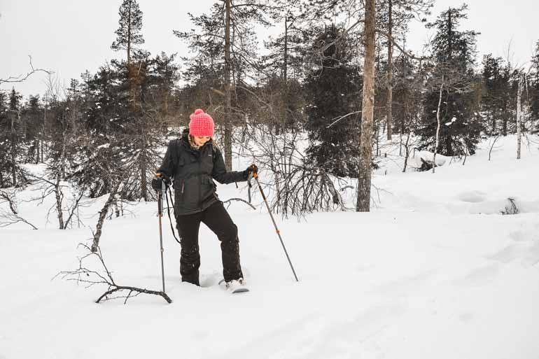 Eine Frau beim Schneeschuhwandern in Finnisch Lappland.