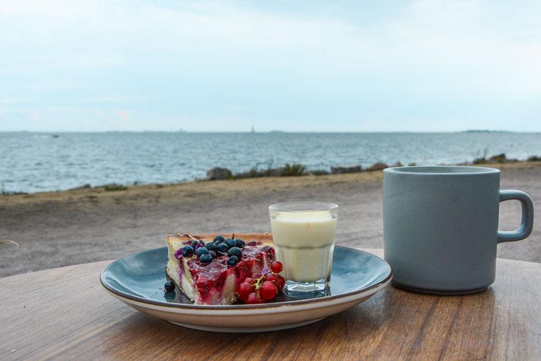 Helsinki: Beerenkuchen auf einem Teller mit einer Tasse neben dran.
