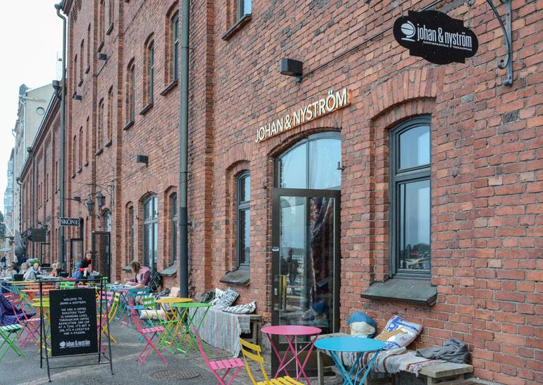 Helsinki: Restaurant mit Backsteinfassade und bunten Stühlen von außen.