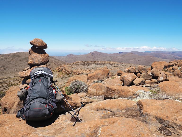 Südafrika Drakensberge: Ein Rucksack steht auf dem Boden, im Hintergrund ein Turm aus Steinen.