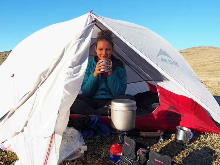 Eine Frau sitzt in einem Zelt.