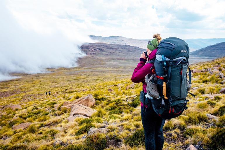 Südafrika Drakensberge: Eine Frau mit einem Rucksack in einem Tal.