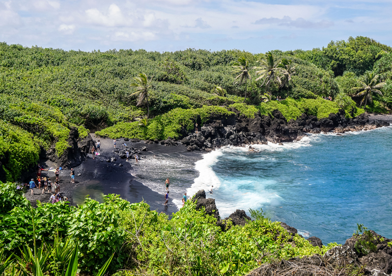 Der Waianapanapa Beach auf Maui Hawaii ist berühmt für seine schwarze Sandfärbung, eine grüne Naturlandschaft rahmt ihn ein.