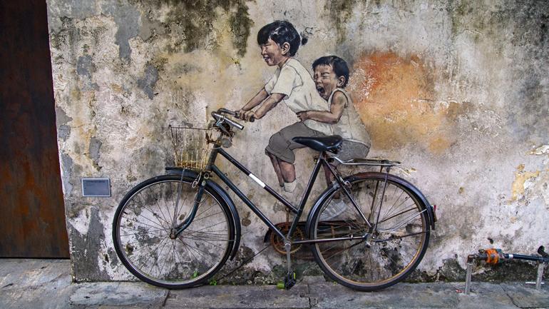 Malaysia: Zwei gezeichnete Kinder sitzen auf einem echten Fahrrad.