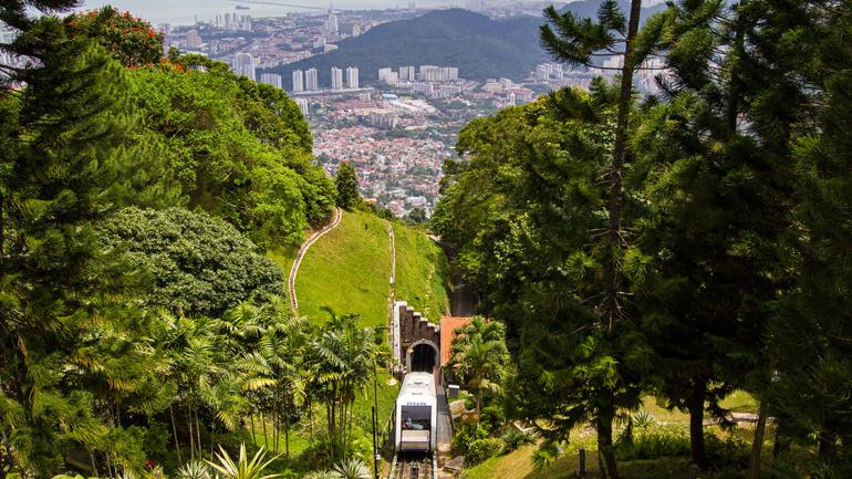 Malaysia: Eine Bahn fährt aus einem Tunnel kommend den Berg hinauf, im Hintergrund die Skyline.