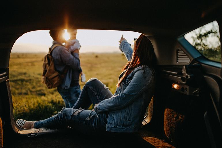 Elternzeit: Eine Frau sitzt im Kofferraum, ein Mann steht mit einem Kind auf dem Arm davor.