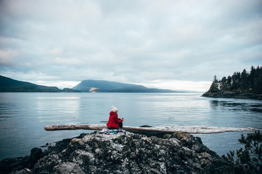 Vancouver Island: Eine Frau mit einer roten Jacke, sitzt auf einem Felsen mit Blick auf das Meer.