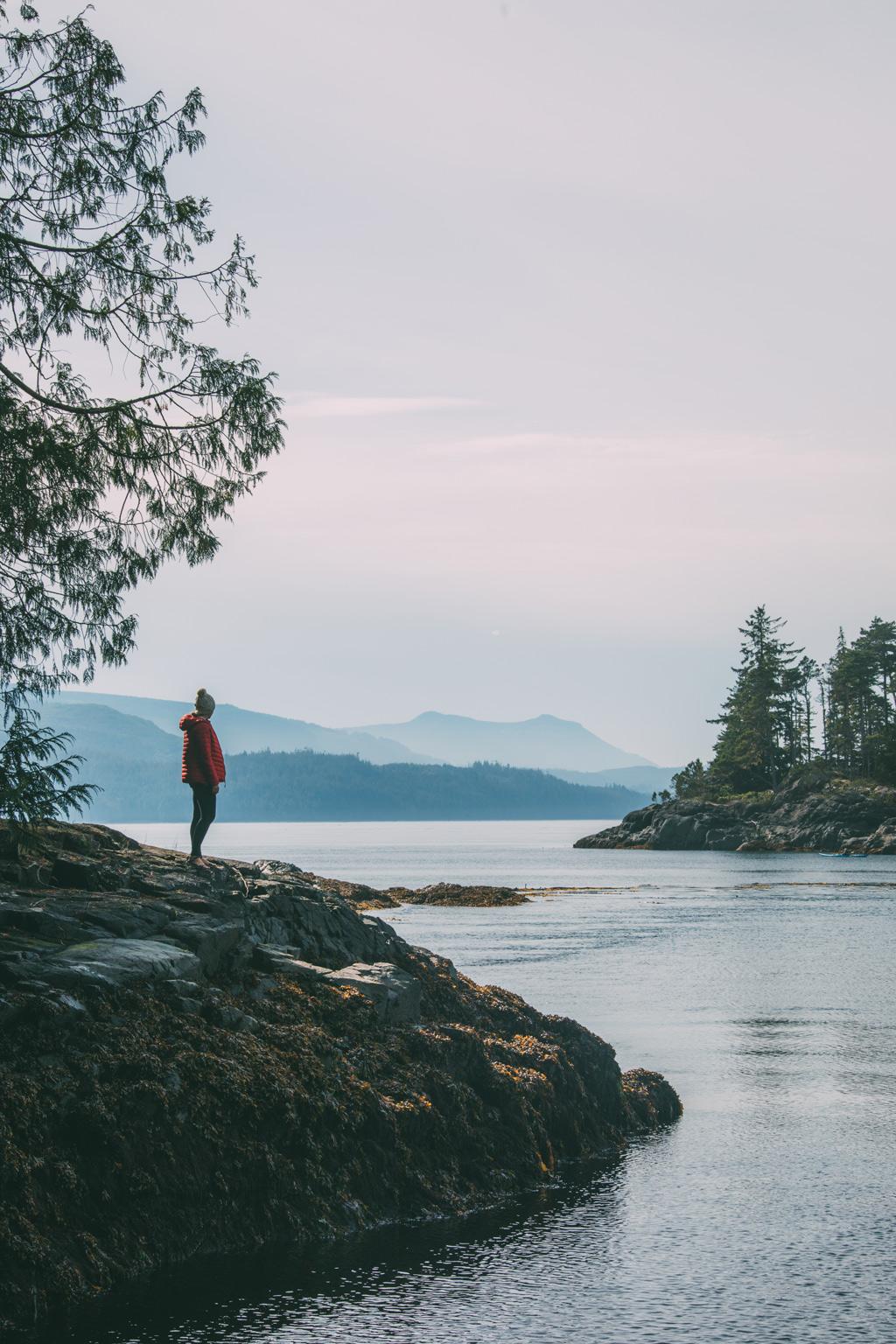 Vancouver Island: Eine Frau steht auf einem Felsen mit Blick auf das Meer.