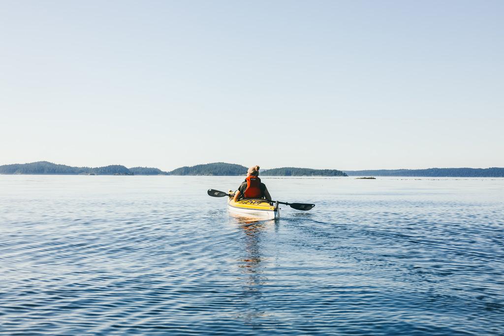 Kayaking Vancouver Island: Eine Frau von hinten auf einem Kajak.
