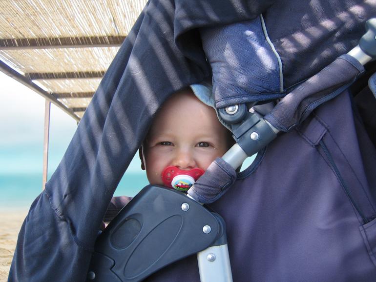 Elternzeit Reise: Kind im Buggy am Meer