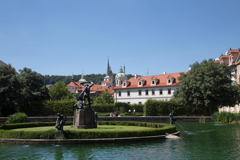 Ein Brunnen der von Wasser Umgeben ist mit einer Villa im Hintergrund