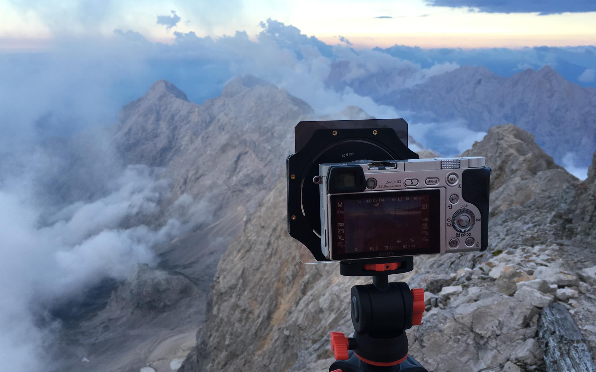 Beste Reisekamera: Eine Kamera steht auf einem Stativ mit Blick auf die Berge.