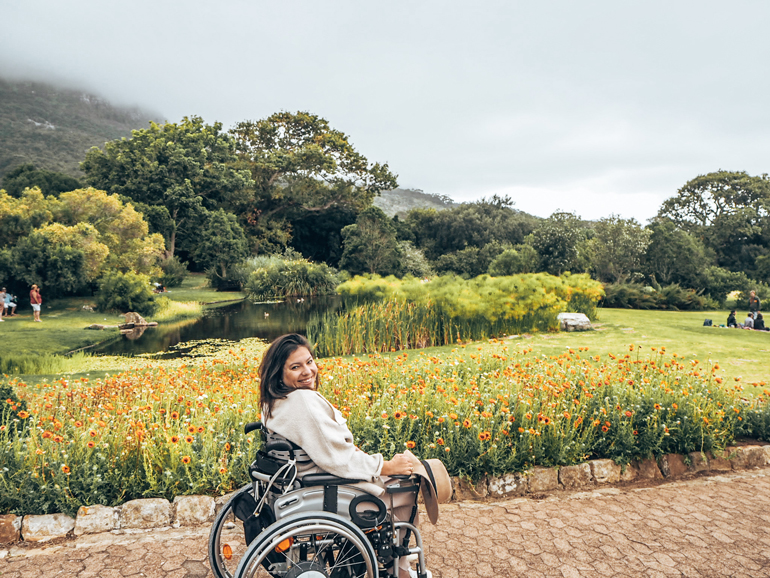 Barrierefrei reisen: Frau im Rollstuhl vor Blumenwiese