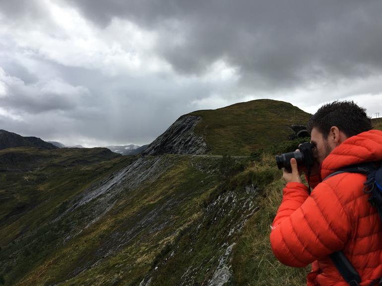Beste Reisekamera: Ein Mann mit einer Roten Jacke hält eine Kamera in der Hand im Hintergrund sind Berge zu sehen.
