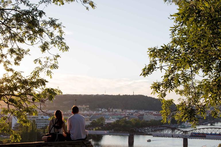 Ein junges Paar genießt den Ausblick auf die Moldau.