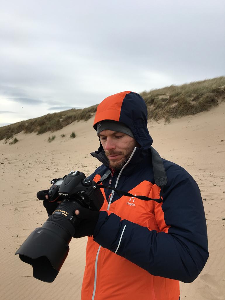 Beste Reisekamera: Ein Mann steht am Strand und hält eine Kamera in der Hand.