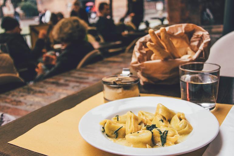 Tipp für Essen in Bologna: Ein angerichteter Teller mit Tortellini auf einem gedecktem Tisch.