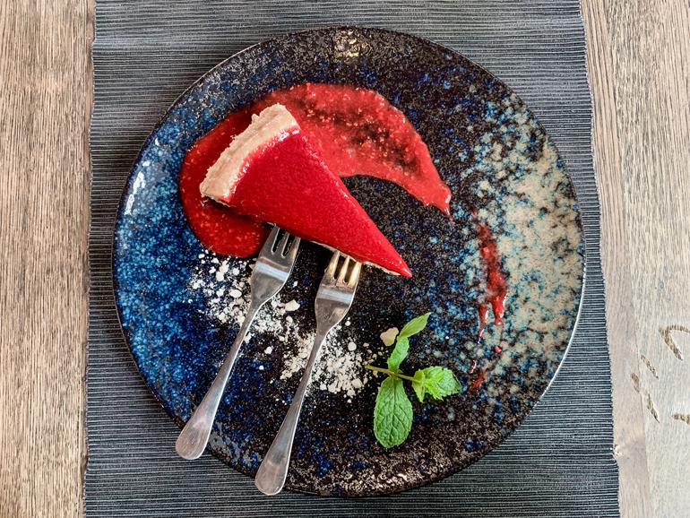 Ein Kuchen auf einem Teller mit zwei Gabeln.