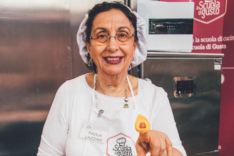 Paola Lazzari, Pastakönigin von Bologna, hält in der Scuola di Gusto eine Tortellini in die Kamera.