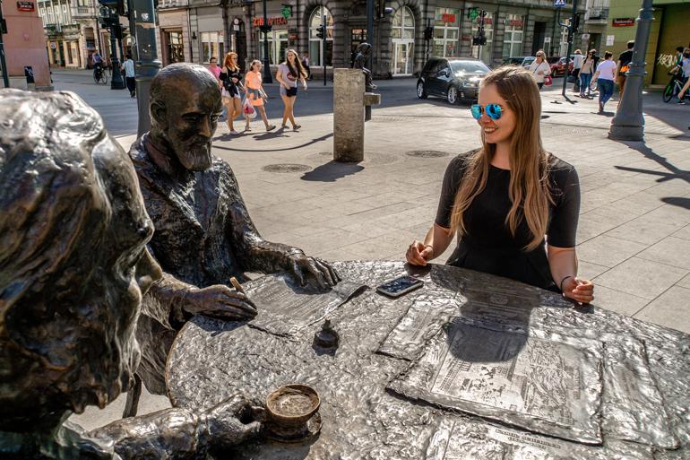 Eine Frau sitzt mit zwei Skulpturen an einem Tisch.