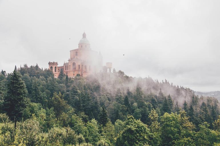 Blick auf die Kirche Santuario della Madonna di San Luca in Bologna, im Wald von Nebel umgeben.