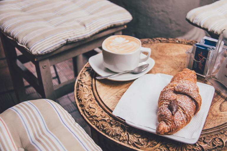 Tipps für gutes Essen in Bologna: Auf einem Tisch steht ein Cappuccino und ein Croissant.