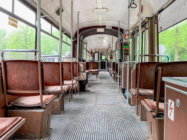 Eine Tram von innen mit roten Sitzen.