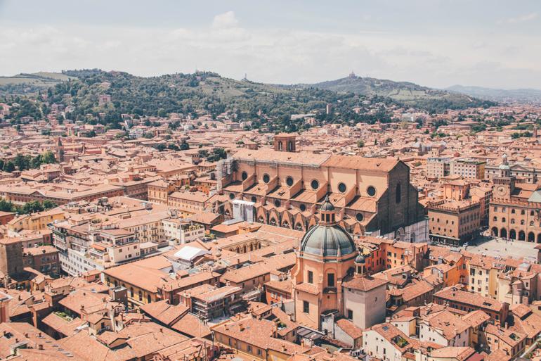 Bologna aus der Vogelperspektive: Ausblick auf orangene Dächer und grüne Berge im Hintergrund.