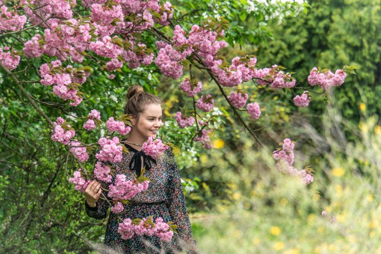 Eine Frau steht zwischen einem Baum an dem rosa Blumen hängen.
