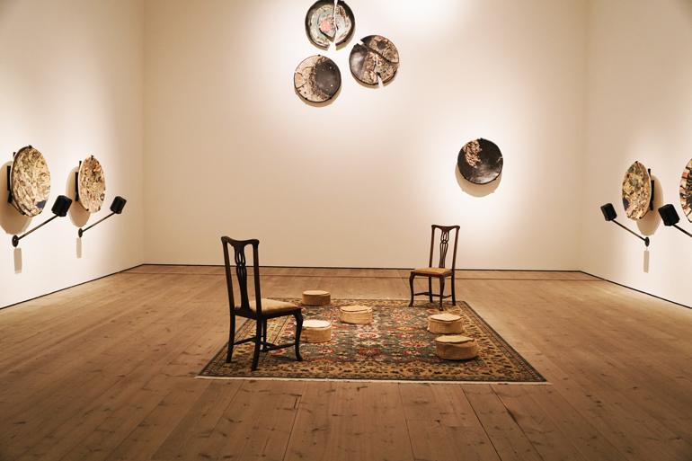 Ein Raum in dem Schüssel aufgehängt sind und zwei Stühle auf einem Teppich stehen.