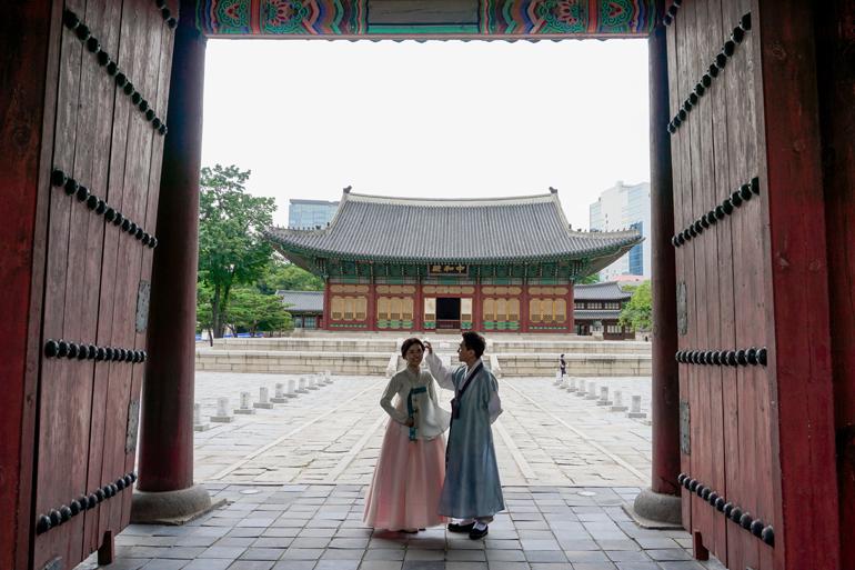 Seoul Sehenswürdigkeiten: Ein Paar steht in traditioneller Kleidung in einem Tor, hinter ihnen befindet sich ein traditionelles Gebäude.