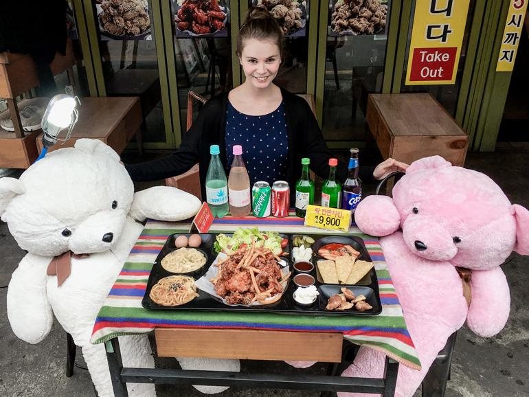 Seoul Sehenswürdigkeiten: Eine Frau sitzt an einem Tisch, vor hier befindet sich allerlei Essen, neben ihr sitzen ein weißer und ein rosafarbener Teddybär.