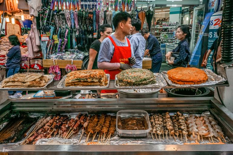 Seoul Sehenswürdigkeiten: Ein Streetfood Stand mit gegrilltem Essen, ein Mann steht dahinter.