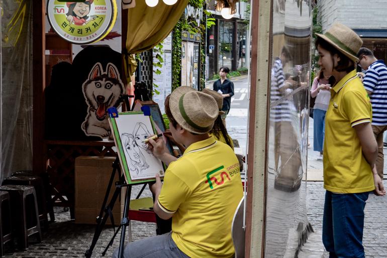 Straßenkunst in Seoul: Ein Mann zeichnet Gesichter auf einem Block, hinter ihm steht eine Frau.
